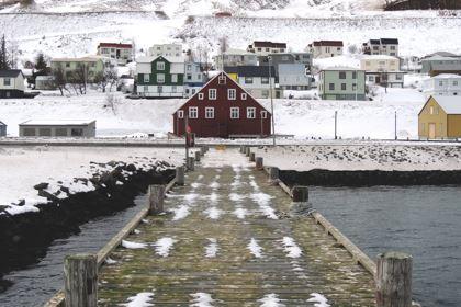 Ein Steg mit rotem Haus vor einer verschneiten Landschaft an einem See in Island.