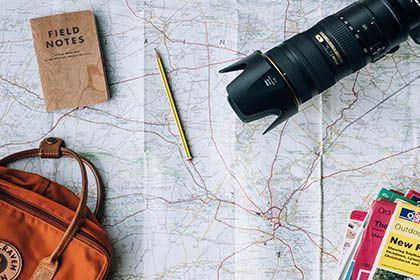 Das Foto zeigt Reisevorbereitungen mit einer Landkarte, Tasche und einem Fotoapparat.