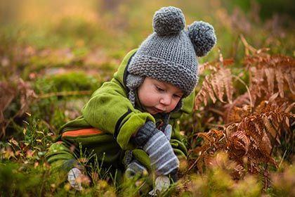 Ein kleines Kind sitzt im Herbstlaub und spielt.