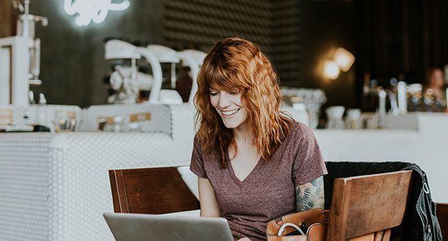 Frau arbeitet fröhlich am Laptop während Sie in einem Cafe´ sitzt.